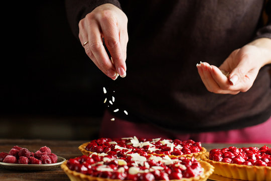 Beautiful freshly made cherry tart decorated with almond chips. Process of making tart. Close up hands of the chef sprinkling cake with almond chips at pastry shop kitchen.