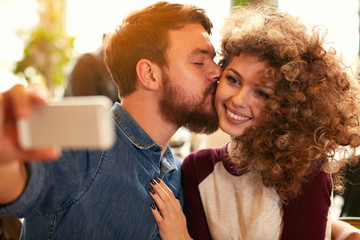 Couple taking selfie while kissing