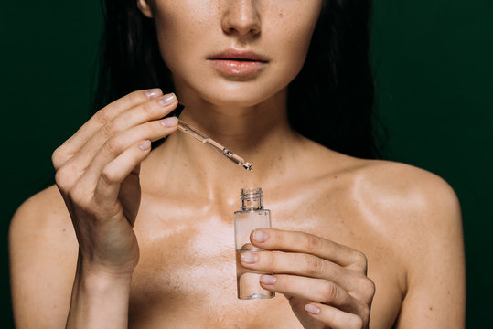 cropped view of naked woman holding bottle with serum isolated on green