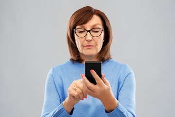 technology and old people concept - senior woman in glasses using smartphone over grey background