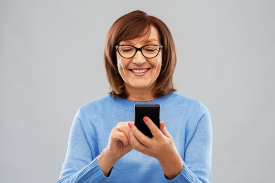 technology and old people concept - smiling senior woman in glasses using smartphone over grey background