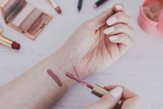 woman's hand holding lipgloss product and testing it surrounded by other make-up items on desk