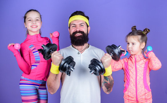 Follow father. Girls cute kids exercising with dumbbells with dad. Motivation and sport example concept. Children repeat exercise after dad. Sport exercise for kids. Healthy upbringing. Sporty family