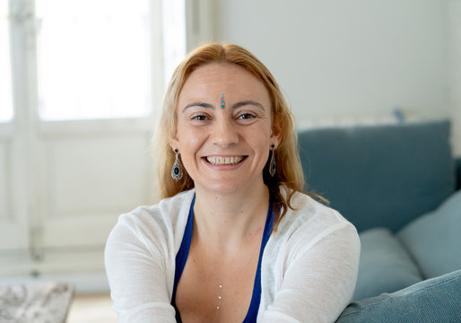 Happy attractive woman with bindi in forehead symbol of third eye chakra in Yoga and mindfulness.