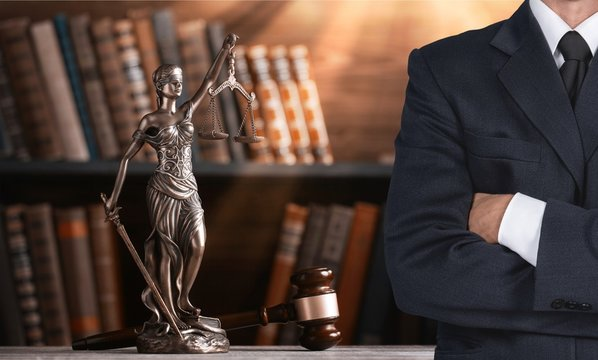 Lawyer standing with crossed arms, Scales of Justice on the background
