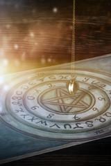 Pendel schwingt über einem Ouijabord in geisterhaftem Licht