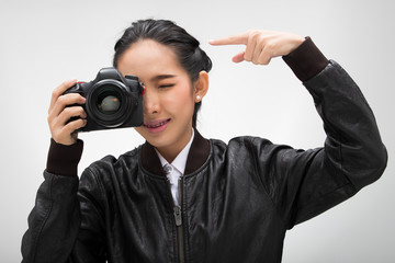 Photographer hold camera with lens point to shoot subject, wear normal dark black leater suit jacket. studio lighting white gradient grey background isolated, point fingers say Hey look at this camera