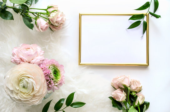 A bouquet of Ranunculus in a vase on a table with a fluffy rug, roses and a frame for demonstrating your beautiful works !  Flat lay, top view mockup. Copy space.