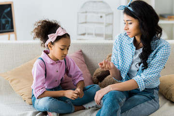 serious african american mother with daughter talking while sitting on sofa