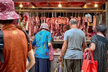 Asian senior people choose fresh meat from street vendor