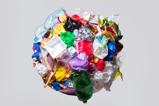 A globe of the earth with trash over white background, the concept of ecology problem and World Environment Day. Photo with message for social advertising, place for inscription