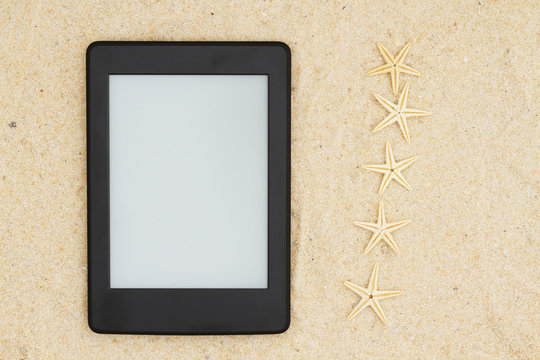 An e-reader on the beach for your summer reading with five starfish