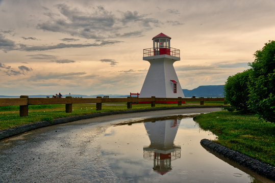 The lighthouse at Carleton, Gaspesie, Quebec reflected in a puddle after a summer storm