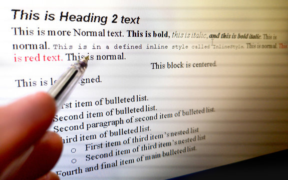 hand with pen indicate text formatting rules on word processor software on computer screen