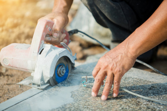 worker cutting granite stone with an diamond electric saw blade and use water to prevent dust and heat