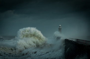 Giant wave break on the Lighthouse at the end of the pier during a storm