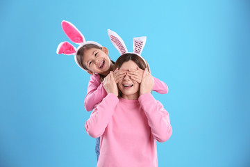 Happy woman and daughter with bunny ears on color background