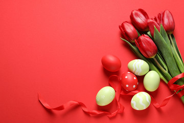 Fotobehang - Flat lay composition of painted Easter eggs and spring flowers on color background, space for text