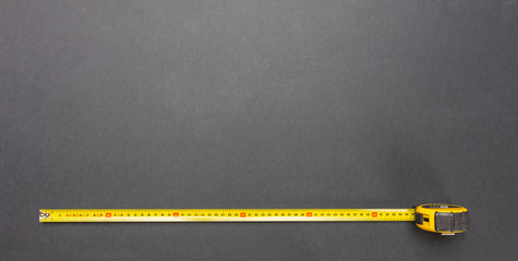Yellow measure tape isolated on black color background, top view, copy space