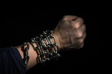 Hands chained in chains isolated on black background