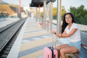 Young Beautiful Asian Tourist Woman Sitting While Waiting At The Train Station