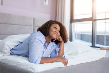 cheerful girl thinking about her boyfriend while resting in the comfortable bed. close up photo. panorama window on the background of the photo. love, feeling, amorousness
