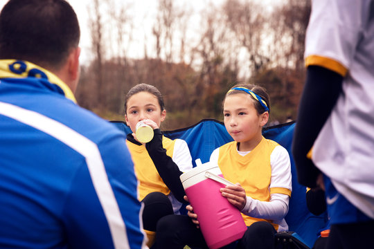 Girls during game break sitting with trainer in playground
