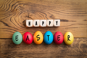 """colored eggs and cubes with letters forming the merssage """"happy easter"""" on wooden background"""