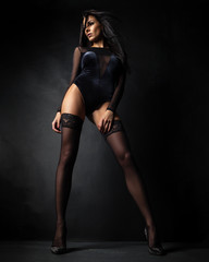 woman in lingerie bodysuit and stockings posing