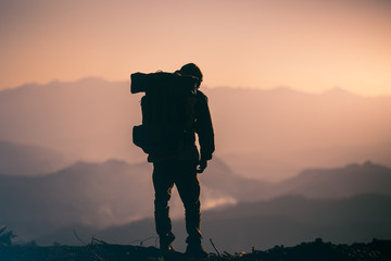 the accomplishment of tourist with backpack standing on the mountain at sunset background. travel silhouette concept.