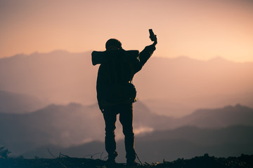Silhouette of young tourist with backpack standing take photo on the mountain. travel concept.