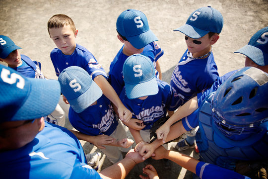 Little league players (8-9) having pep talk with coach