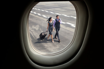 Man and woman walking to plane on tarmac