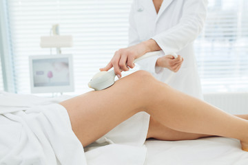 Unrecognizable female cosmetologist doing Rf lifting procedure on woman s long slim legs in a beauty parlor. Treatment of overweight and flabby skin.