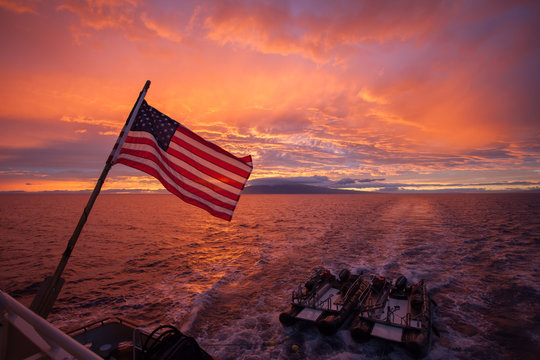 American flag in front of a beautiful ocean sunset landscape