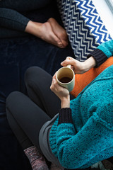 Mid adult woman sitting on sofa and drinking tea low section