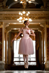 Beautiful ballerina dancing and jumping in a luxurious hall in a pink dress.