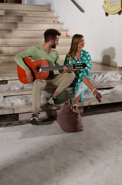 Couple of young people sitting on the steps. The guy with a beard, green shirt, while he plays the guitar. The smiling blonde girl in a 3/4 sleeved shirt with a pleated polka dot skirt on aqua-green