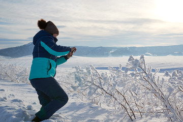 Woman taking a picture of the view with a mobile phone. Field and forest, mountains covered with snow. Blue sky. Frosty day.