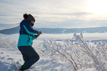 Woman taking a picture of the view with a mobile phone. Field and forest, mountains covered with snow. Blue sky.