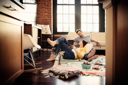 Mid adult couple relaxing with book at home date