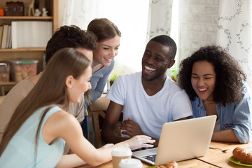 Happy diverse friends watching comedy movie, funny video on laptop