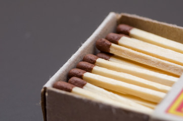 Matches in box, dark background. Macro photography. Close-up shot. Matches in open match-box on black background