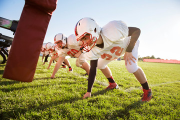 Teenage football players (14-15, 16-17) tackling in school field