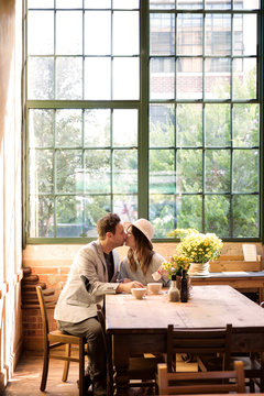 Mid adult couple kissing in cafe