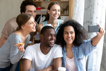 Happy smiling multiracial friends making selfie photo in pizzeria