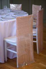 Vertical shot of sitting arrangement at a fine dining restaurant or event featuring transparent plates glassware and silverware in the order of use with white table cloth and chairs with sequin covers