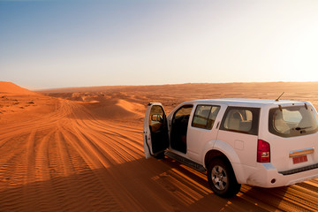 Off-road vehicle in the wahiba sands desert dunes at sunset (Oman)