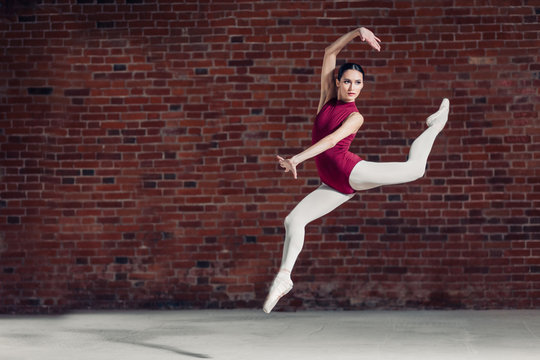 in bright white studio. Young dancer performing a jump in the air, stylish ballet dance, copy space