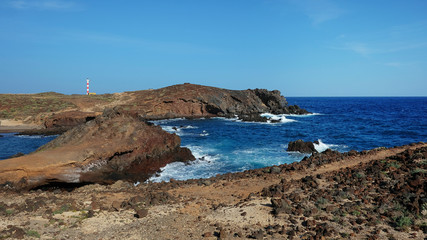 Most typical coastal landscape of the southern part of Tenerife island showing a very arid volcanic terrain with strong frothy waves and crystal clean ocean and sunny clear skies all year round, Spain